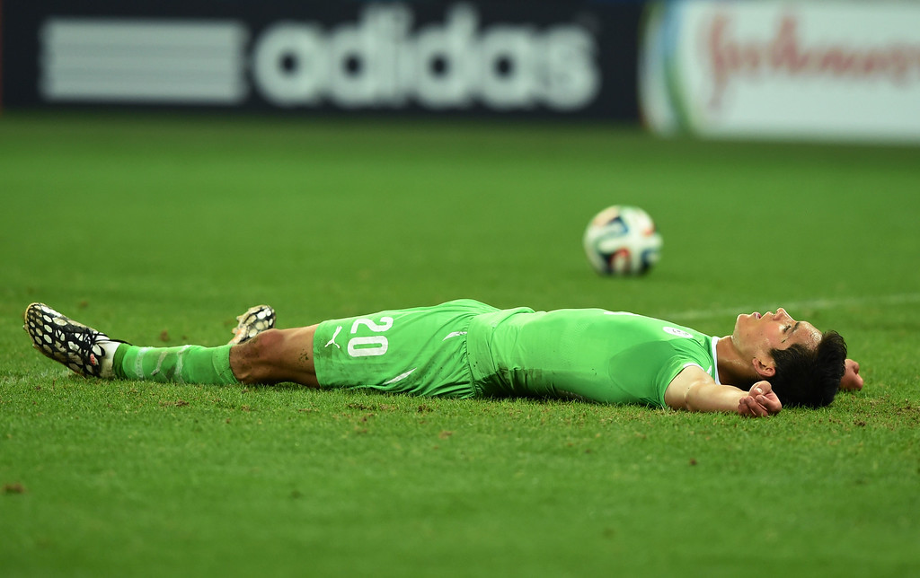 . Aissa Mandi of Algeria lies on the field after a goal by Germany in extra time during the 2014 FIFA World Cup Brazil Round of 16 match between Germany and Algeria at Estadio Beira-Rio on June 30, 2014 in Porto Alegre, Brazil.  (Photo by Matthias Hangst/Getty Images)