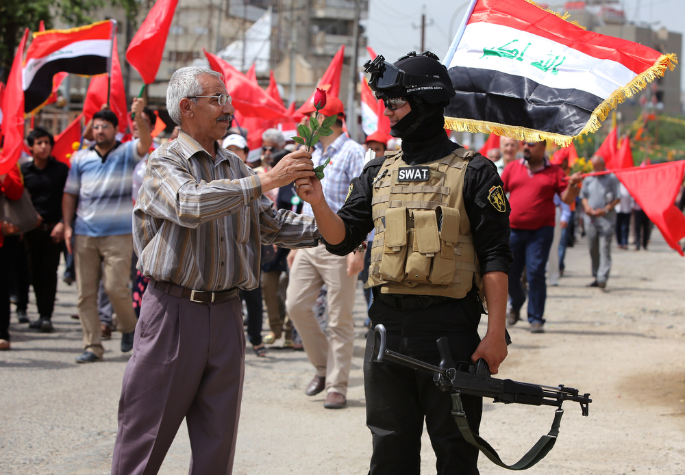 . An Iraqi civilian gives a rose to a member of the security forces during a march organized by the Iraqi communist party to celebrate International Workers Day, also known as Labour Day, on May 1, 2014 in the capital Baghdad. (AHMAD AL-RUBAYE/AFP/Getty Images)