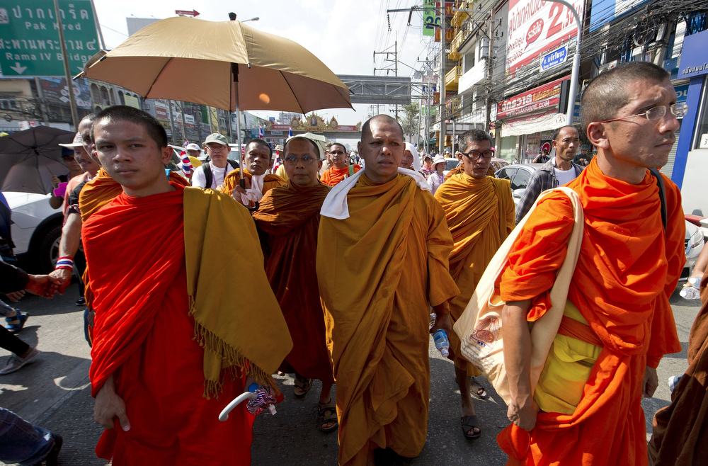 """. Buddhist monks parade with anti-government protesters during a rally in Bangkok on January 13, 2014. Thai opposition protesters launched their attempted \""""shutdown\"""" of Bangkok, occupying key intersections in the capital in an escalation of their campaign to unseat Prime Minister Yingluck Shinawatra. (PORNCHAI KITTIWONGSAKUL/AFP/Getty Images)"""