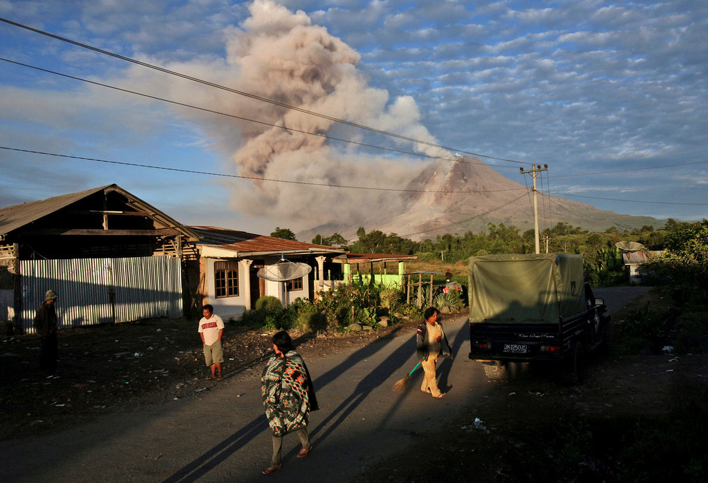 . Villagers start their morning routine as Mount Sinabung releases volcanic materials into the air in Perteguhan, North Sumatra, Indonesia, Monday, Jan. 6, 2014. The 2,600-meter (8,530-foot) volcano has sporadically erupted since September. Authorities extended a danger zone around a rumbling volcano in western Indonesia on Sunday after it spewed blistering gas farther than expected, sending panicked residents streaming down the sides of the mountain. (AP Photo/Binsar Bakkara)
