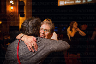 Louise Chernin, president and CEO of the Greater Seattle Business Association, gets a congratulatory hug for being honored with the Lifetime Achievement Award at the Puget Sound Business Journal's The Business Of Pride event at the Paramount Theatre in Seattle on Thursday, May 26, 2016. (BUSINESS JOURNAL PHOTO | Dan DeLong)