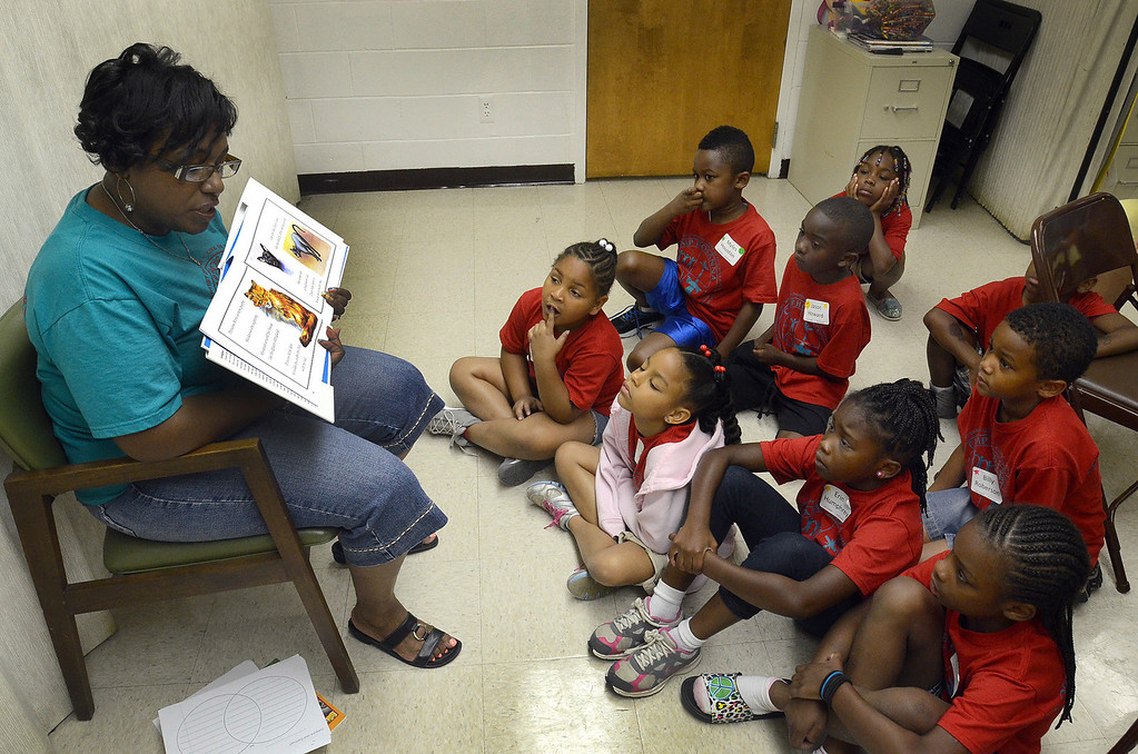 . Jennifer Graham, of Detroit, reads to kids during the free Camp Hosanna at New Bethel Missionary Baptist Church in Pontiac, Monday July 22, 2013. (Oakland Press Photo:Vaughn Gurganian)