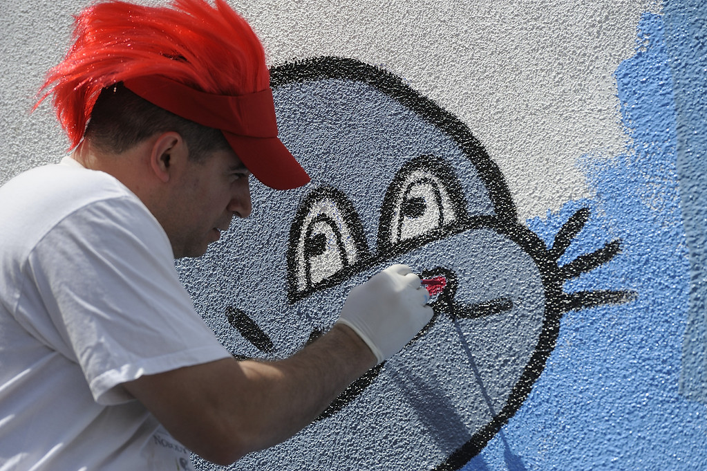 . LONG BEACH, CALIF. USA -- Francisco Rodriguez puts the finishing touches on a mural during a one-day playground build at Edison Elementary School in Long Beach, Calif., on April 6, 2013.  More than 200 volunteers from the Long Beach Unified School District, Green Long Beach! and Zynga, joined organizers from KaBOOM! and residents to build a new playground at the Edison Child Development Center.  The playground is the fourth built by KaBOOM! and Zynga.org and is one of more than 150 playground builds KaBOOM! will lead across the country in 2013 in an effort to fulfill its vision of a great place to play within walking distance of every child in America. Photo by Jeff Gritchen / Los Angeles Newspaper Group