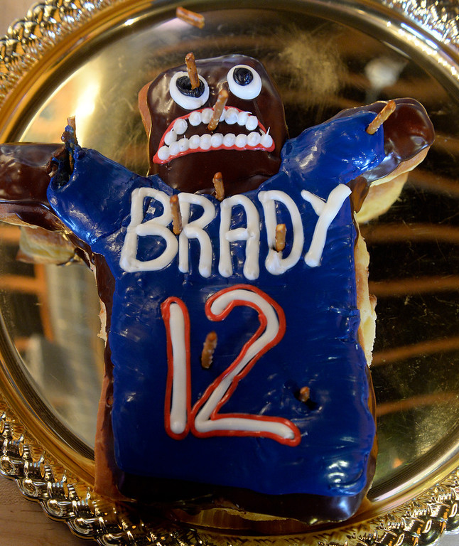 . Closeup of the Tom Brady voodoo doughnut at Voodoo Doughnut. The store held its grand opening at it\'s new 1520 E. Colfax Ave location in Denver on Wednesday, January 15, 2014.  Customers were allowed to poke the doughnut with pretzels. (Denver Post Photo by Cyrus McCrimmon)