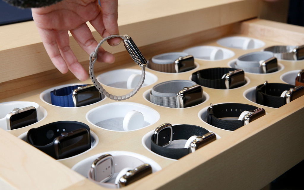 . A customer picks up an Apple Watch at an Apple Store in Hong Kong Friday, April 10, 2015. From Beijing to Paris to San Francisco, the Apple Watch made its debut Friday. Customers were invited to try them on in stores and order them online. (AP Photo/Kin Cheung)