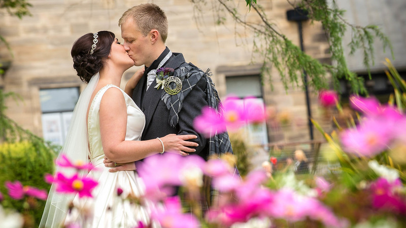 Wedding Photography of Laura & Kevin, Dean Park Hotel, Kirkcaldy  Photography is of the Bride & Groom kissing behind a field of bright colours
