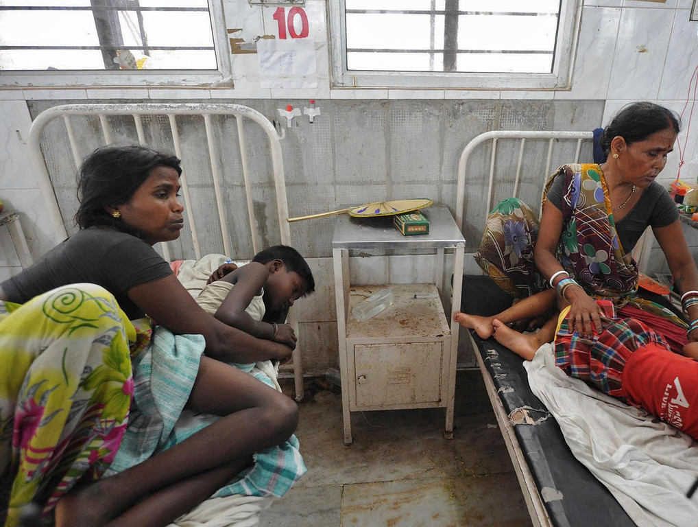 . Women sit next to their sick children who consumed spurious meals at a school on Tuesday, at a hospital in the eastern Indian city of Patna July 17, 2013. At least 20 children died and dozens were taken to hospital with apparent food poisoning after eating a meal provided for free at their school in the district of Chapra in the eastern Indian state of Bihar, the education minister said on Wednesday, sparking violent protests.  REUTERS/Krishna Murari Kishan