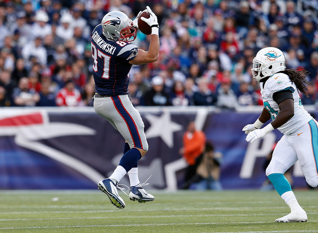 . Rob Gronkowski #87 of the New England Patriots catches a pass as Dannell Ellerbe #59 of the Miami Dolphins defends in the first half at Gillette Stadium on October 27, 2013 in Foxboro, Massachusetts. (Photo by Jim Rogash/Getty Images)