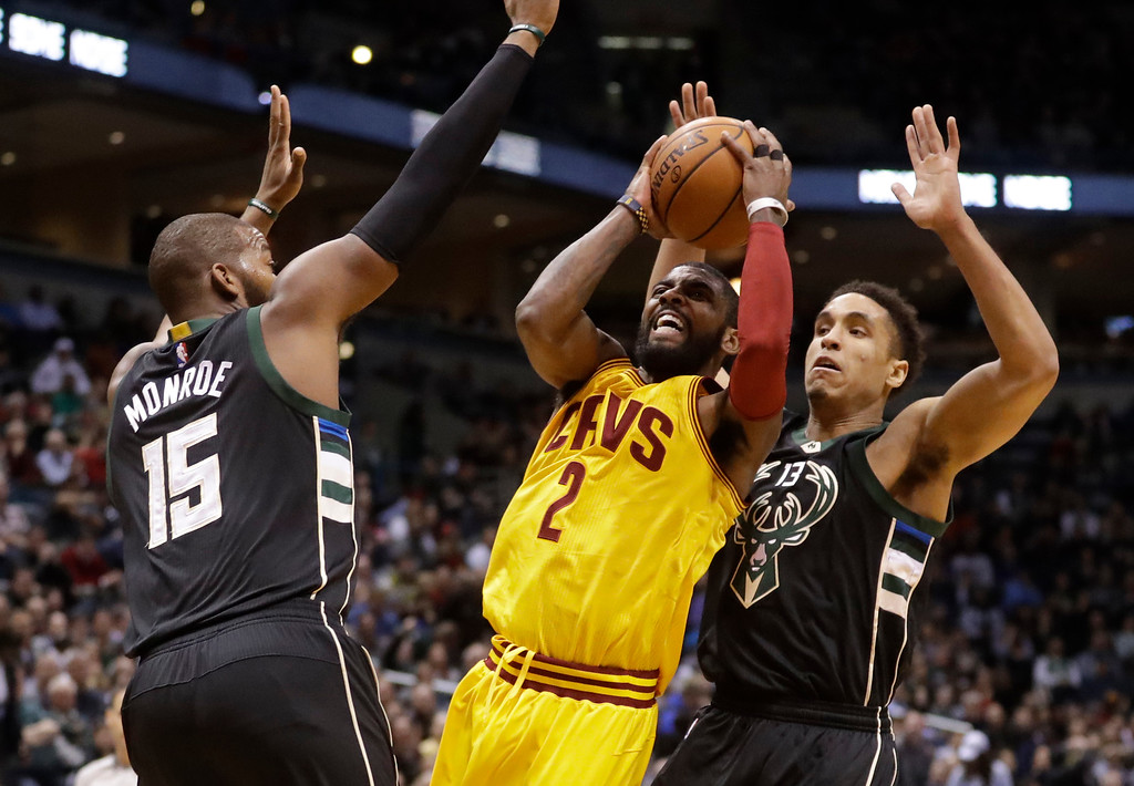 . Cleveland Cavaliers\' Kyrie Irving shoots between Milwaukee Bucks\' Greg Monroe and Malcolm Brogdon during the first half of an NBA basketball game Tuesday, Dec. 20, 2016, in Milwaukee. (AP Photo/Morry Gash)