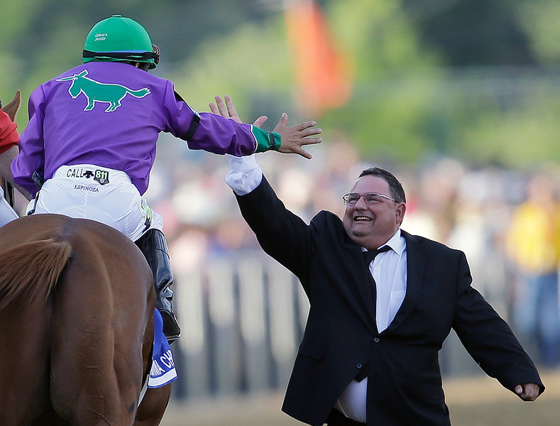 . Assistant trainer Alan Sherman slaps hands with jockey Victor Espinoza after California Chrome won the 139th Preakness Stakes horse race at Pimlico Race Course, Saturday, May 17, 2014, in Baltimore.  (AP Photo/Patrick Semansky)