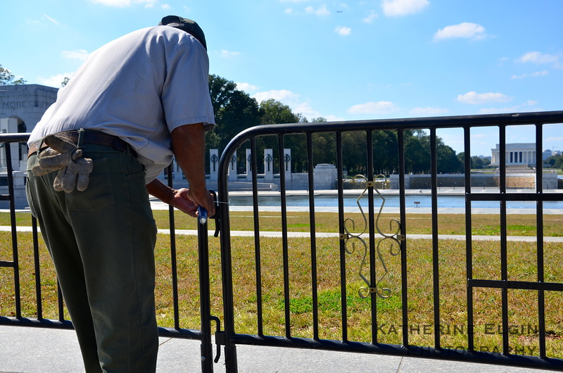 A member of the National Park Service reinforces the barricades blocking off the World War II memorial after a group of veterans supported by Congressmen and others entered the public space.