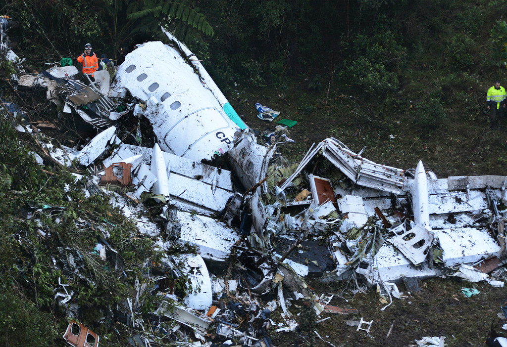 . Rescue workers stand at the wreckage site of a chartered airplane that crashed in a mountainous area outside Medellin, Colombia, Tuesday, Nov. 29, 2016. The plane was carrying the Brazilian first division soccer club Chapecoense team that was on it\'s way for a Copa Sudamericana final match against Colombia\'s Atletico Nacional. (AP Photo/Luis Benavides)