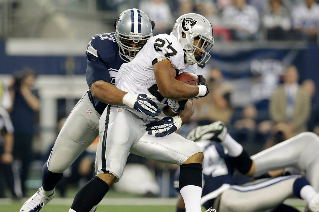 . Oakland Raiders running back Rashad Jennings (27) is tackled by Dallas Cowboys defensive tackle Jason Hatcher (97) during the first half of an NFL football game, Thursday, Nov. 28, 2013, in Arlington, Texas.  (AP Photo/LM Otero)