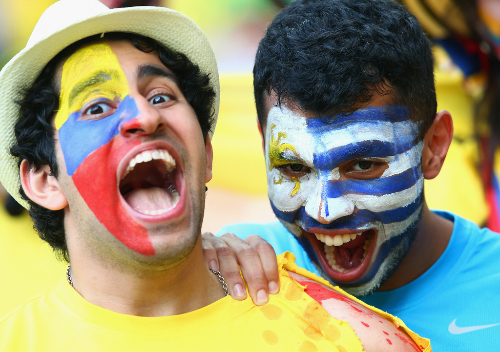 . RIO DE JANEIRO, BRAZIL - JUNE 28:  A Uruguay fan pretends to bite the shoulder of a Colombian fan ahead of  the 2014 FIFA World Cup Brazil round of 16 match between Colombia and Uruguay at Maracana on June 28, 2014 in Rio de Janeiro, Brazil.  (Photo by Julian Finney/Getty Images)