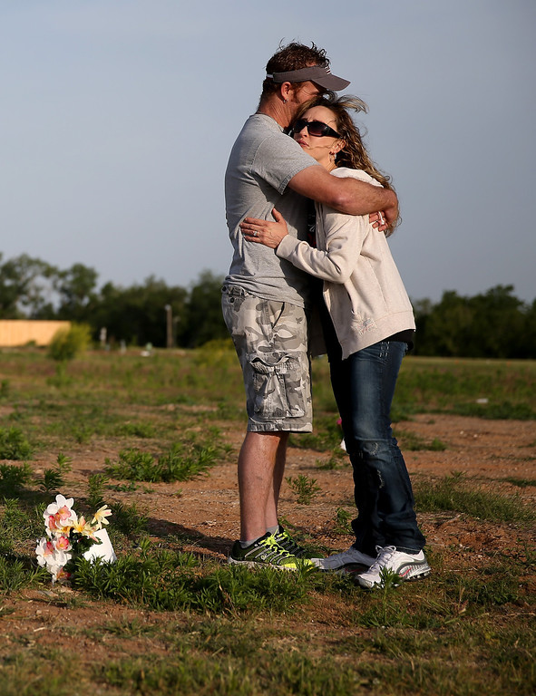 . David Friess and his wife Ann Friess hug after placing flowers in the ground where their house used to be and where one of their dead dogs was found in the rubble one year ago when a tornado passed through the area on May 20, 2014 in Moore, Oklahoma.  On May 20, 2013 a two-mile wide EF5 tornado touched down in the town killing 24 people and leaving behind extensive damage to homes and businesses.  (Photo by Joe Raedle/Getty Images)