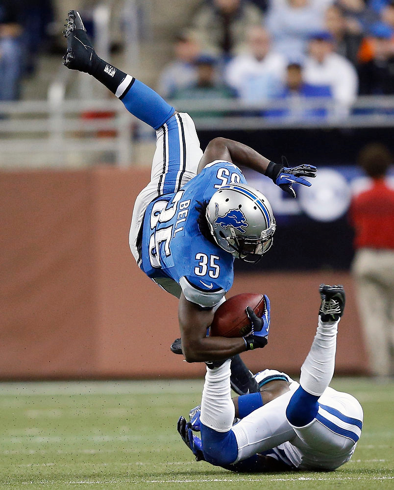 . Detroit Lions running back Joique Bell (35) is upended by Indianapolis Colts cornerback Vontae Davis during the third quarter of an NFL football game at Ford Field in Detroit, Sunday, Dec. 2, 2012. (AP Photo/Rick Osentoski)
