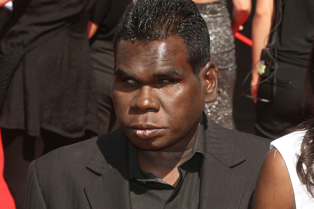 . FILE - In this Nov. 27, 2011, file photo, aboriginal singer Geoffrey Gurrumul Yunupingu, left, arrives for the Australian Record Industry Association awards in Sydney, Australia. Yunupingu, renowned for singing in his native Yolngu language with a heart-rending voice and a unique guitar-playing style has died, his recording label said Wednesday, July 26, 2017. He was 46. (AP Photo/Rob Griffith, File)