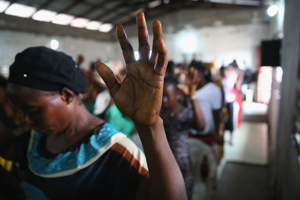 . A congregation prays during a Sunday service at the Bethel World Outreach Church in the West Point township on January 25, 2015 in Monrovia, Liberia. With Ebola cases now in single digits nationwide, many Liberians have begun to return to normal life. The Liberian government and international aid agencies, however, are urging the public to remain vigilant until the disease is fully eradicated in West Africa.  (Photo by John Moore/Getty Images)