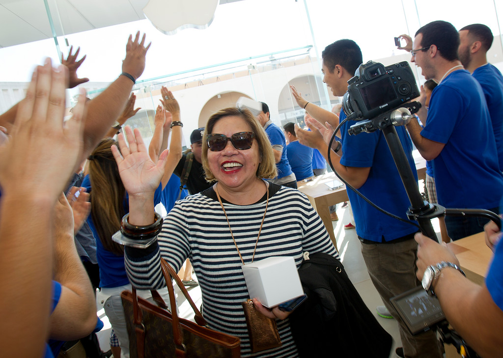 . Lily San Agustin is greeted by Apple store staff as she enters the redesigned Apple Store at the Stanford Shopping Center in Palo Alto, Calif., on Saturday, Sept. 7, 2013.  (LiPo Ching/Bay Area News Group)