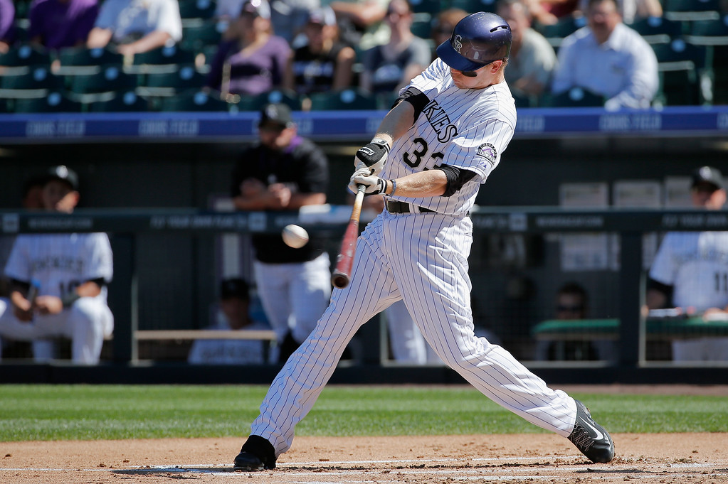 . DENVER, CO - SEPTEMBER 17:  Justin Morneau #33 of the Colorado Rockies hits a three run home run off of Carlos Frias #77 of the Los Angeles Dodgers to give the Rockies a 3-0 lead in the first inning at Coors Field on September 17, 2014 in Denver, Colorado.  (Photo by Doug Pensinger/Getty Images)