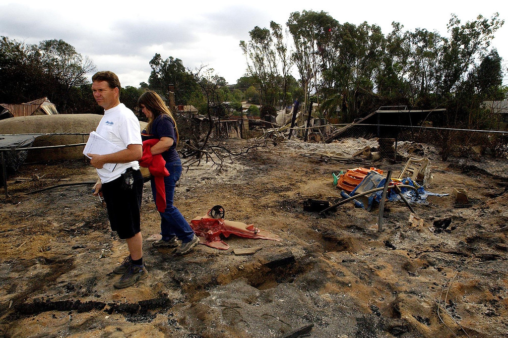 . Russ and Sandi Wilson survey the remains of thier destroyed home Thursday, Oct. 30, 2003 in Crest, Calif. Numerous homes were destroyed by the Cedar Fire which continues to burn just outside San Diego. (AP Photo/Matt York)