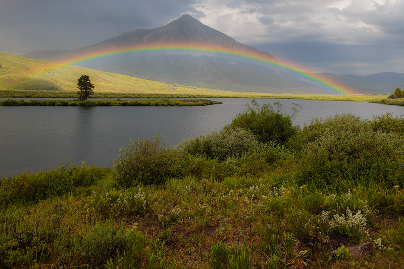 Rainbow over Peanut Lake with Mount Crested Butte in background.