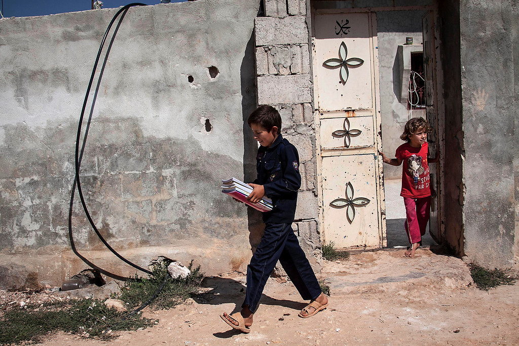. In this Sunday, Sept. 29, 2013 photo, 12-year-old Abdo al-Fikri, walks to school from his family home in Madaya village as classes begin in the Idlib province countryside of Syria. It has been a year since al-Fikri and his siblings were last in school. The area has seen ongoing battles between opposition forces and troops loyal to President Bashar Assad, and like pretty much everything else in Madaya, the school was forced to shut down because of the violence. (AP Photo)