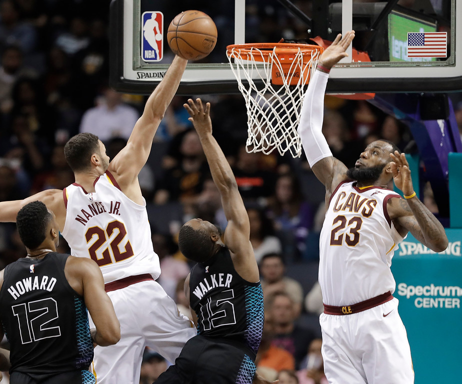 . Charlotte Hornets\' Kemba Walker (15) shoots between Cleveland Cavaliers\' LeBron James (23) and Larry Nance Jr. (22) during the second half of an NBA basketball game in Charlotte, N.C., Wednesday, March 28, 2018. (AP Photo/Chuck Burton)