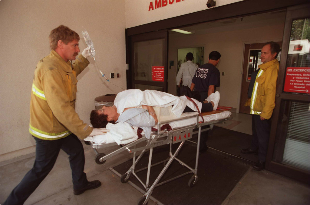 . A female adult victim is led into Holy Cross Hospital by paramedics.  She was shot in the arm and abdomen.  Five victims, three male children and two female adults, were shot at the North Valley Jewish Community Center in Granada Hills, California Tuesday morning, August 10, 1999.   Los Angeles Daily News file photo.