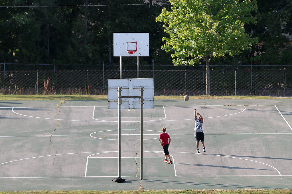 . A couple of kids enjoy the warm weather on Tuesday ion Leominster to play some basketball on some courts just off of Johnson Street. SENTINEL & ENTERPRISE/JOHN LOVE