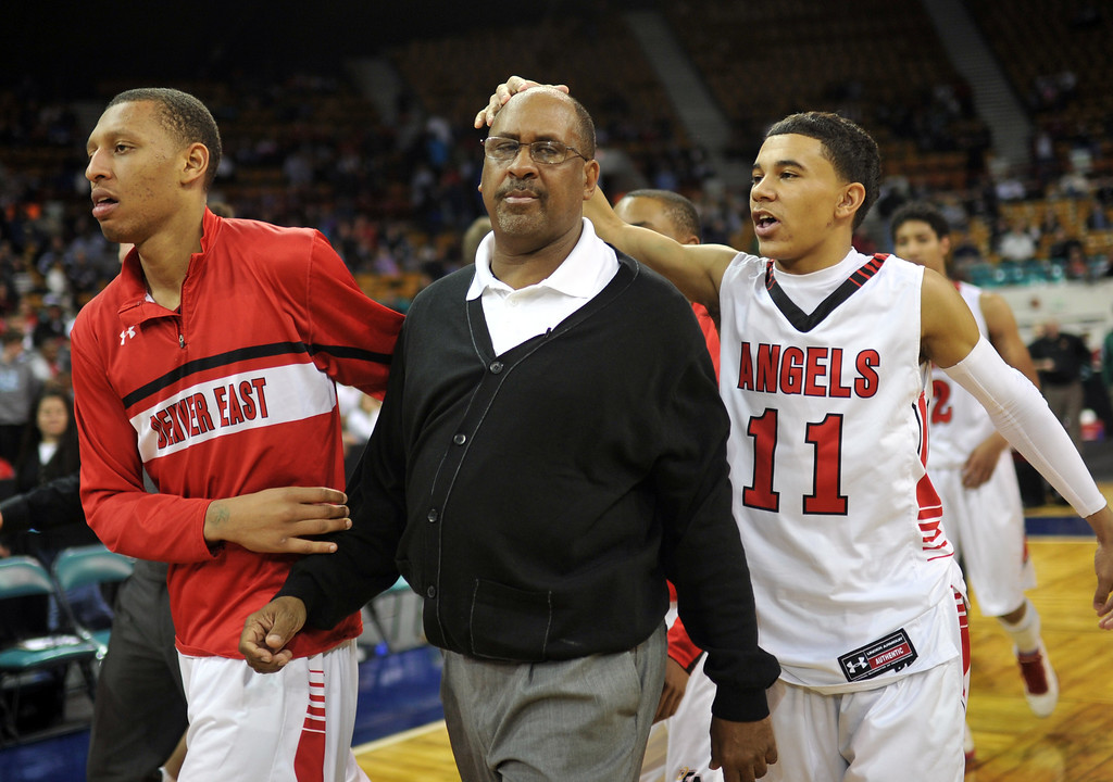 . DENVER, CO. - MARCH 08: Denver East High School boy\'s basketball team head coach Rudy Carey, center, celebrates his 700th win with Brian Carey #11, right, and Tyre Robinson #32, left, at Denver Coliseum. East High School won the 5A state quarter final game against Arapahoe High School by 60-55. March 8, 2013. Denver, Colorado. (Photo By Hyoung Chang/The Denver Post)