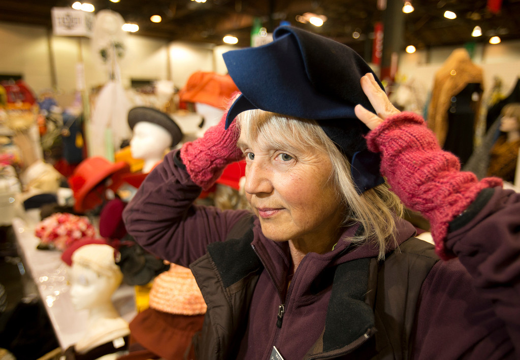 . Pam Dos Remedios-Litke, accessories chair for the annual White Elephant Sale, tries on a vintage hat that will be part of the fundraiser for the Oakland Museum of California, at the Oakland Museum Women\'s Board 96,000-square-foot warehouse in Oakland, Calif., Tuesday, Jan. 15, 2013. (D. Ross Cameron/Staff)