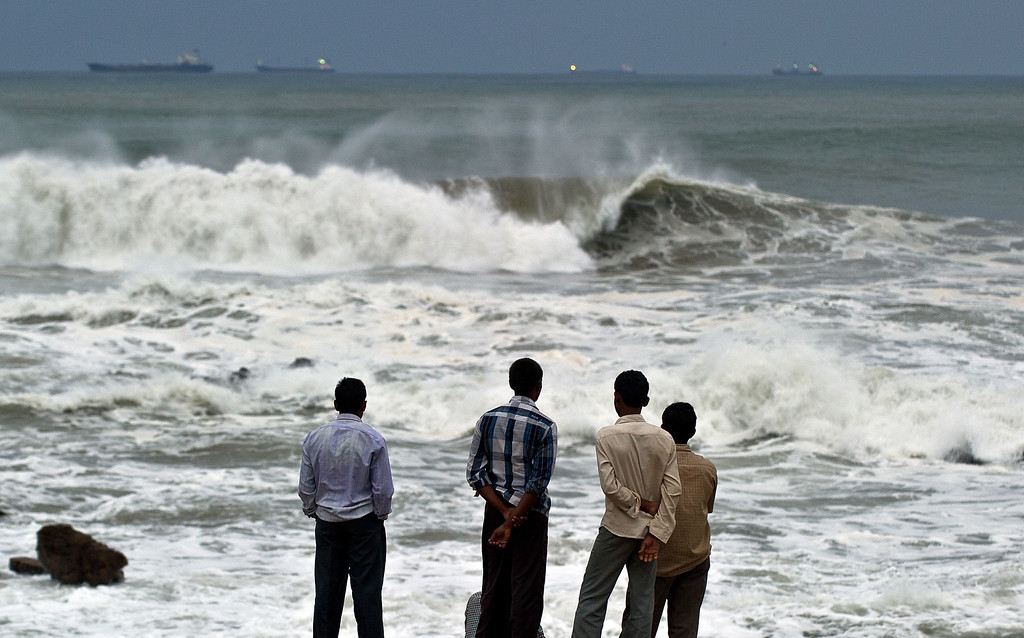 . Indian youth stand on the shore as high tidal waves hit the coastline in Visakhapatnam on October 12, 2013. Tens of thousands of terrified villagers braced for the arrival of a massive cyclone bearing down on India\'s east coast on October 12, packing winds of up 220 kilometres an hour (140 mph).  MANAN VATSYAYANA/AFP/Getty Images