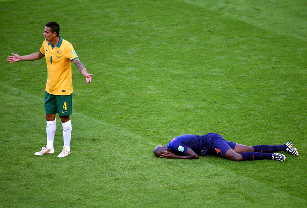 . Tim Cahill of Australia reacts after a challenge on Bruno Martins Indi of the Netherlands during the 2014 FIFA World Cup Brazil Group B match between Australia and Netherlands at Estadio Beira-Rio on June 18, 2014 in Porto Alegre, Brazil.  (Photo by Paul Gilham/Getty Images)