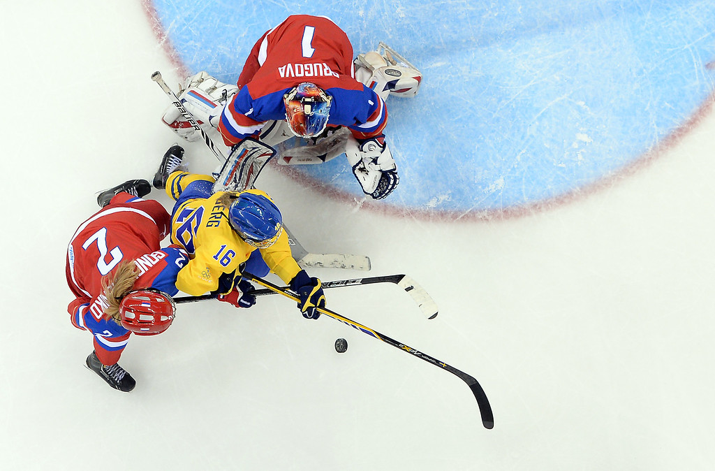 . Sweden\'s Pernilla Winberg (C) vies with Russia\'s goalkeeper Anna Prugova (R) and Russia\'s Angelina Goncharenko during the Women\'s Ice Hockey Group B match Sweden vs Russia at the Shayba Arena at the Sochi Winter Olympics on February 13, 2014 in Sochi.   ANDREJ ISAKOVIC/AFP/Getty Images