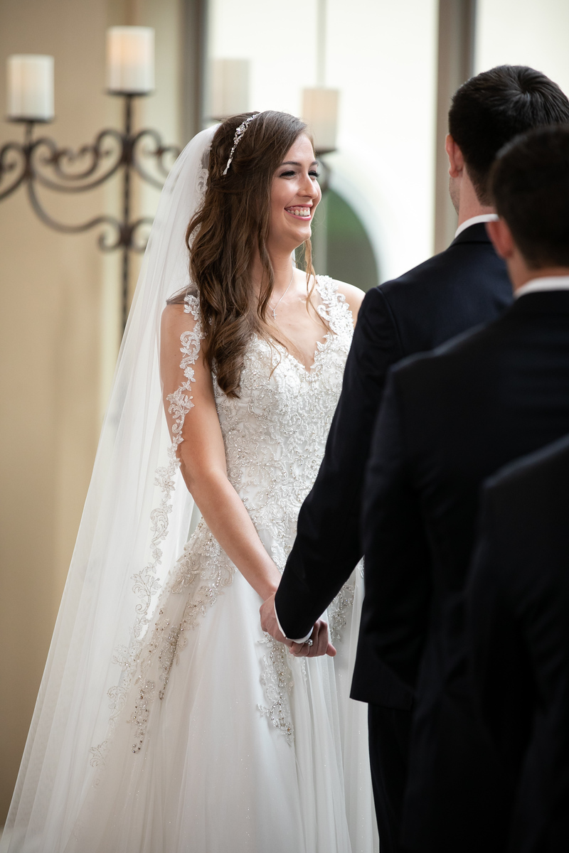 a bride smiling at her groom as they hold hands at an altar on their wedding day
