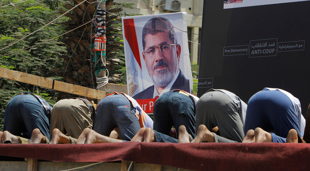 ". Supporters of Egypt\'s ousted President Mohammed Morsi pray in front of his poster in Nahda Square, where protesters have installed their camp near Cairo University in Giza, southwestern Cairo, Egypt, Monday, Aug. 12, 2013. Egyptian authorities on Monday postponed a move to disperse two Cairo sit-ins by supporters of the country\'s ousted president to ""avoid bloodshed,\"" an official said, as Islamist supporters stepped up rallies to demand his return to power. (AP Photo/Amr Nabil)"