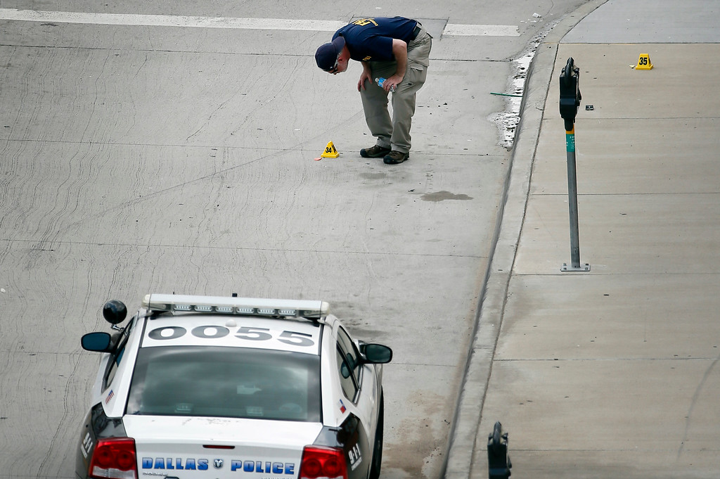 . A member of an FBI evidence response team looks down at a piece of marked evidence on the sidewalk in front of Dallas police headquarters where a gunman staged an attack on police early Saturday June 13, 2015, in Dallas.  A man suspected of spraying Dallas Police Headquarters with gunfire early on Saturday has been found dead in a van after a police sniper shot him and pipe bombs found in the vehicle were exploded, a police spokesman said.  (AP Photo/Tony Gutierrez)