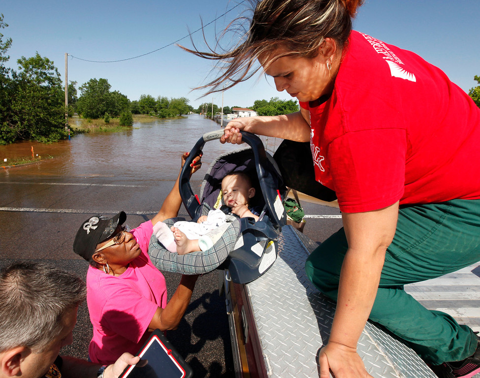 . Riley Webb hands her seven month old baby Bryce Webb down to Oklahoma County Commissioner Willa Johnson after being rescued by Midwest City Fire Dept. personnel from a flooded mobile home park off of Air Depot Blvd. between NE 10th and NE 23rd St. in Midwest City, Okla, Saturday, June 1, 2013, after up to eight inches of rain fell during the previous 24 hours. (AP Photo/The Oklahoman, Paul Hellstern)