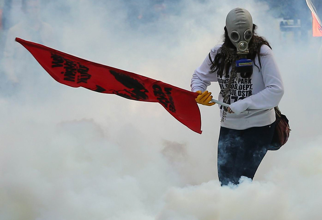 . A person holds a flag as police uses tear gas and water cannon on October 7, 2014 in Ankara against demonstrators who protest against attacks launched by Islamic State insurgents targeting the Syrian city of Kobane and lack of action by the government. ADEM ALTAN/AFP/Getty Images