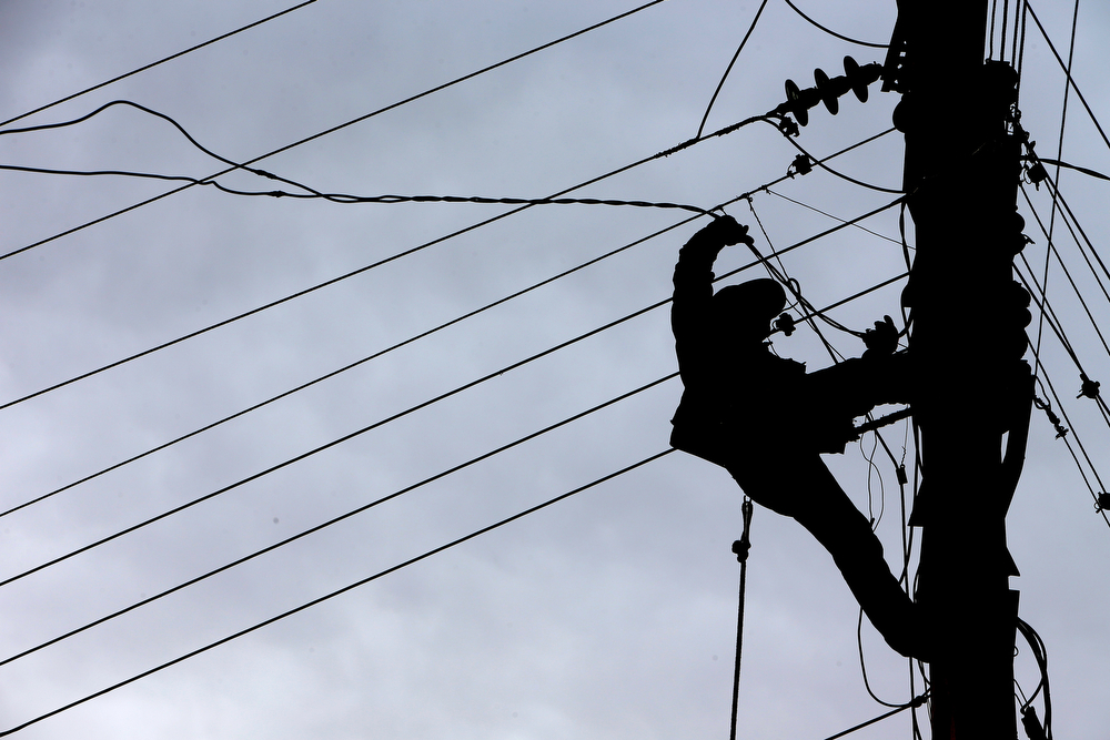 . A Lebanese electricity worker fixes power cables, at the site where a deadly car bomb exploded Saturday evening, in the predominately Shiite town of Hermel, about 10 miles (16 kilometers) from the Syrian border in northeast Lebanon, Sunday, Feb. 2, 2014. (AP Photo/Hussein Malla)