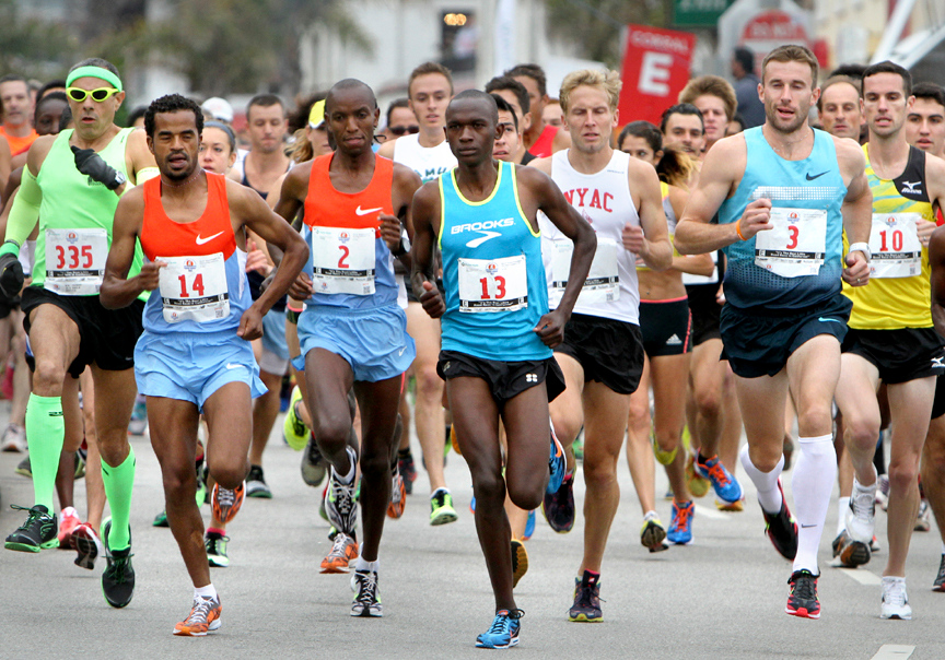 . Wharf to Wharf winner Nelson Oyugi (13) leads the charge as runners burst off the starting line of the 2013 Wharf to Wharf race on Beach Street in Santa Cruz on Sunday morning. (Kevin Johnson/Sentinel)