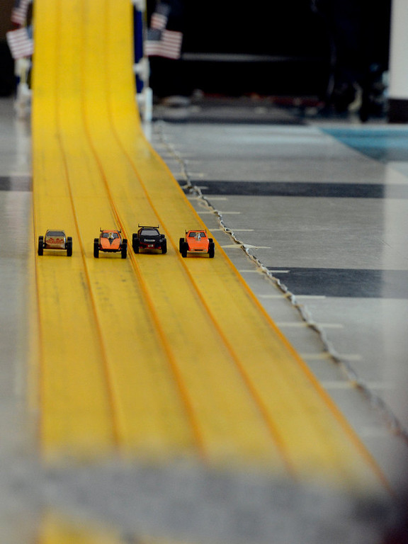 . COMMERCE CITY, CO. - JANUARY 26: Contestants  cars race down the track as they head to the finish line during the 2013 Pack 414 Pinewood Derby races at Ortho Stuart Middle School January 26, 2013 in Commerce City. The pinewood cars weigh 5 oz and are 7 inches long. The cars take about 3 second to go down the track.  The scouts can either buy a kit with the car already shaped or buy a block of wood and carve their own.  (Photo By John Leyba / The Denver Post)