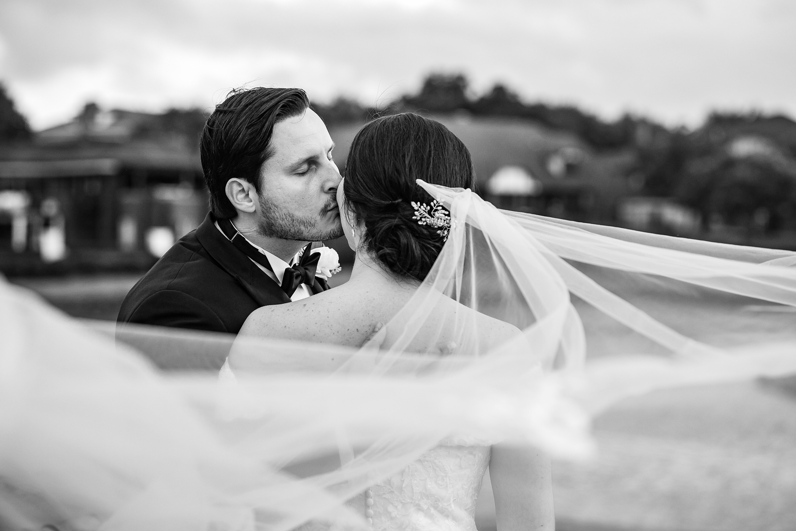 black and white photo of a groom kissing his wife on the cheek as her veil whips around in the wind