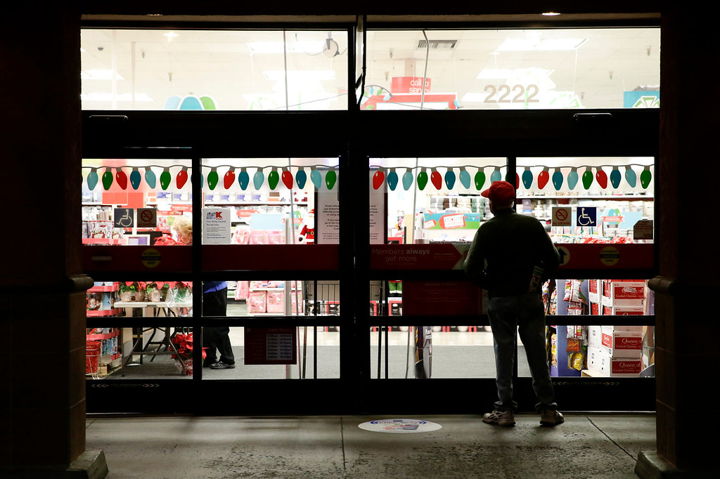 . A shopper who declined to give his name waits outside a Kmart store for it to open on Thursday, Nov. 28, 2013, in Anaheim, Calif.  Instead of waiting for Black Friday, which is typically the year\'s biggest shopping day, more than a dozen major retailers are opening on Thanksgiving day this year. (AP Photo/Jae C. Hong)