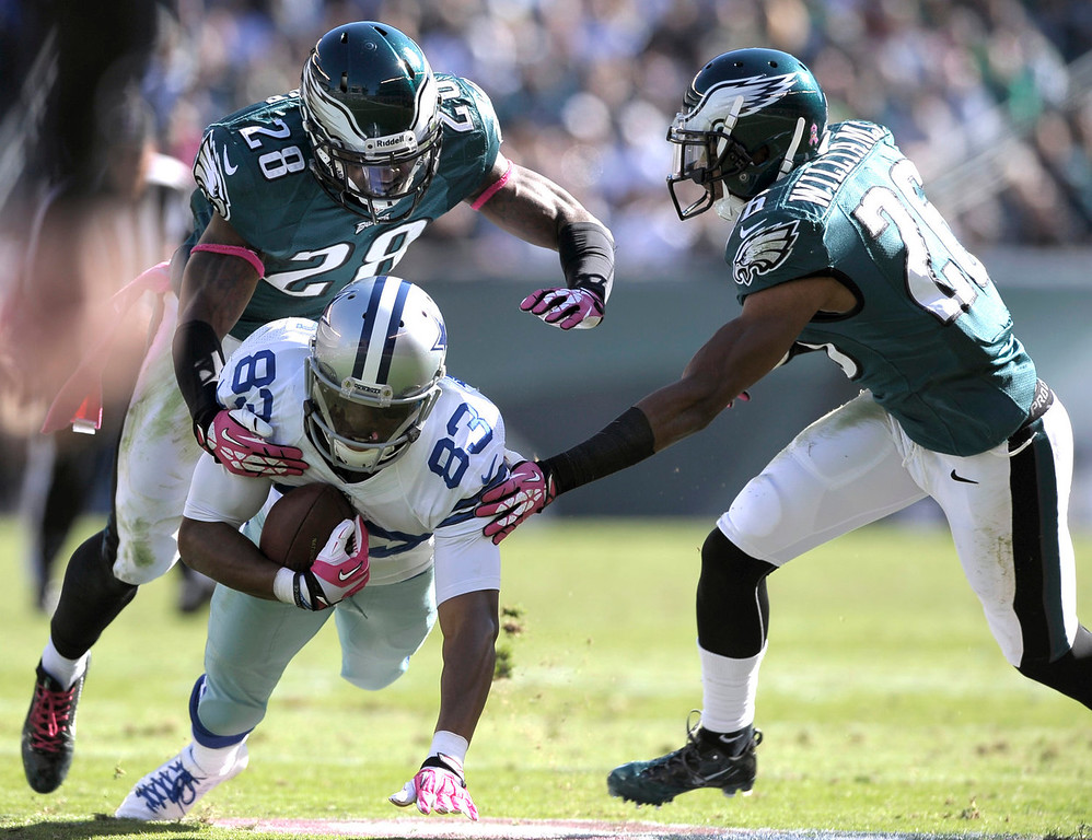 . Dallas Cowboys wide receiver Terrance Williams (83) is brought down by Philadelphia Eagles free safety Earl Wolff (28) and cornerback Cary Williams during the first half of an NFL football game Sunday, Oct. 20, 2013, in Philadelphia. (AP Photo/Michael Perez)