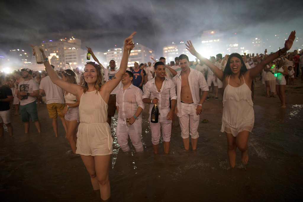 . People react as they watch fireworks exploding over Copacabana beach during New Year\'s celebrations in Rio de Janeiro, Brazil, Monday, Jan. 1, 2018. (AP Photo/Leo Correa)