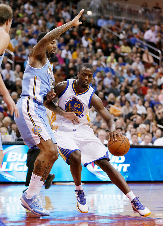 . Golden State Warriors forward Harrison Barnes, right, drives to the basket past Denver Nuggets forward Wilson Chandler during the first half of a preseason NBA basketball game, Thursday, Oct. 16, 2014, in Des Moines, Iowa. (AP Photo/Charlie Neibergall)