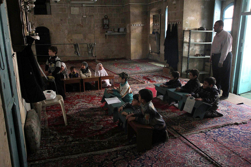. A group of children attends a lesson conducted by activists, who say they provide basic education for children after schools were closed in the city, in a mosque in Aleppo March 23, 2013. REUTERS/ Giath Taha