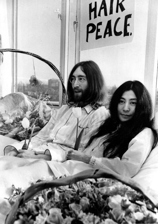 . Beatle John Lennon and his wife, Yoko Ono, hold a bed-in for peace in room 902, the presidential suite at the Hilton Hotel in Amsterdam on March 25, 1969.  The newlyweds, holding solitary tulips, begin a seven-day Love-In to protest the Vietnam War.  (AP Photo)